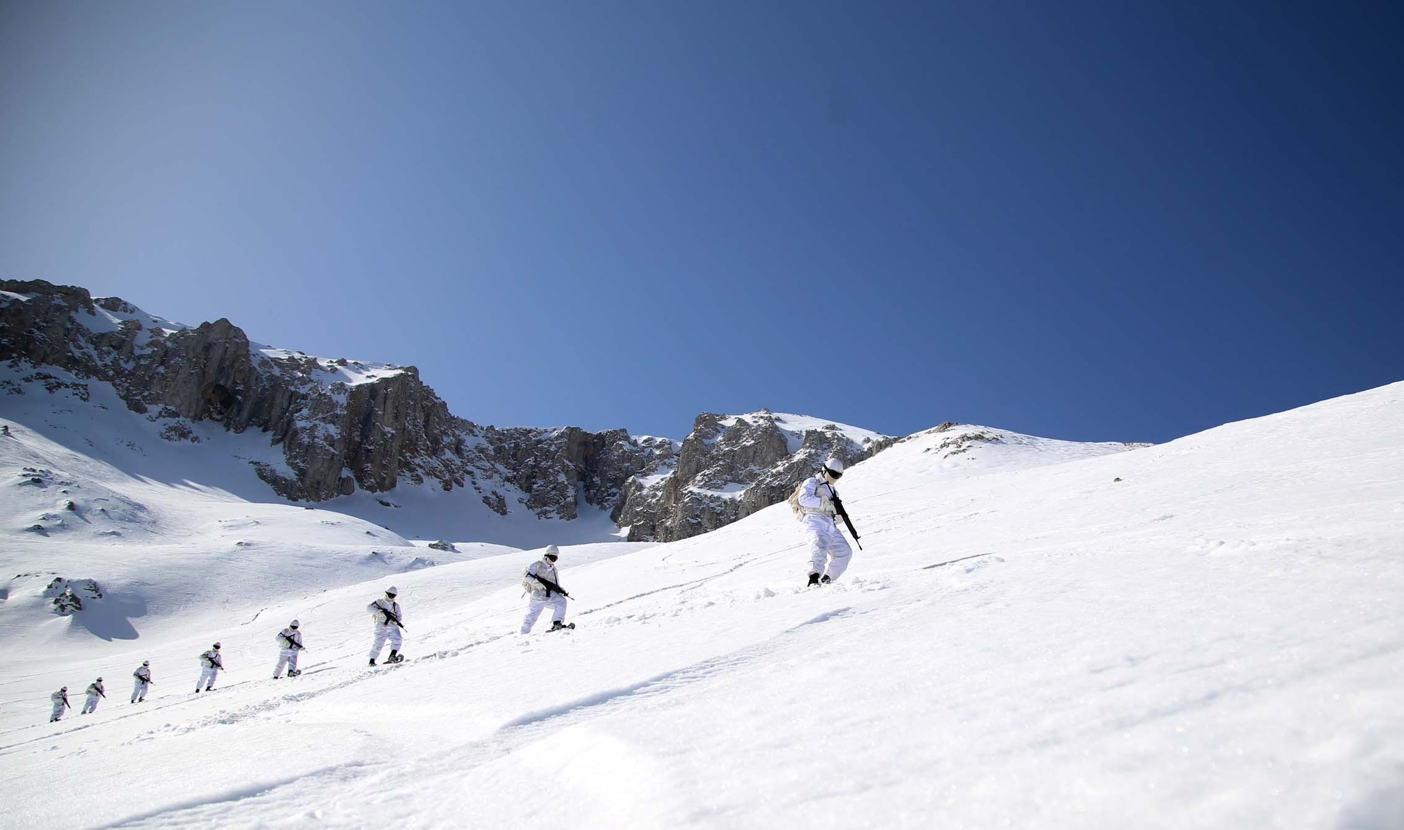 Prospective commandos walk in single file on a snowy slope.