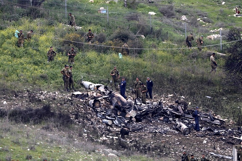 Israeli soldiers inspect the remains of an Israeli F-16 fighter jet that was shot down after a hit by Syrian anti-aircraft system, near the northern Israeli collective community of Harduf. (EPA Photo)