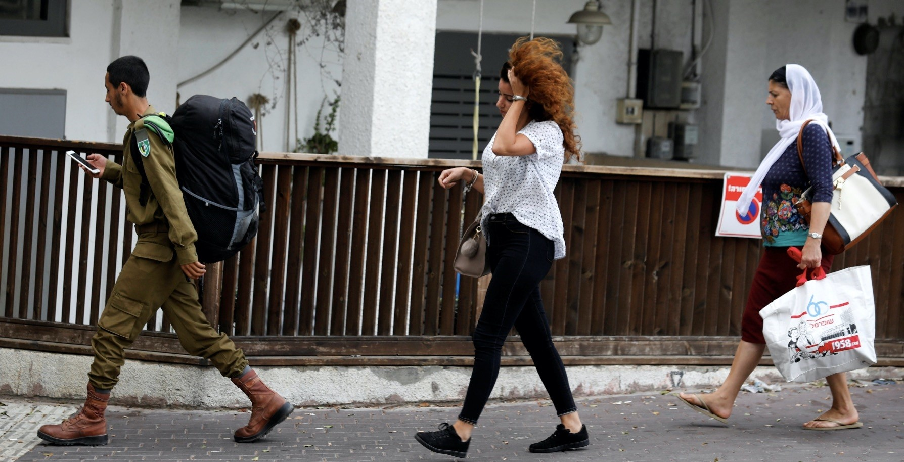 An Israeli soldier from the Druze minority walks past others in the Druze town of Daliat al-Karmel, northern Israel, Aug. 2.