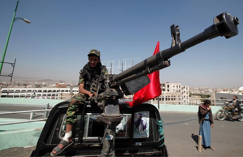 A Houthi militant sits atop a police patrol truck stationed on a bridge in the capital Sanaa (Reuters Photo)