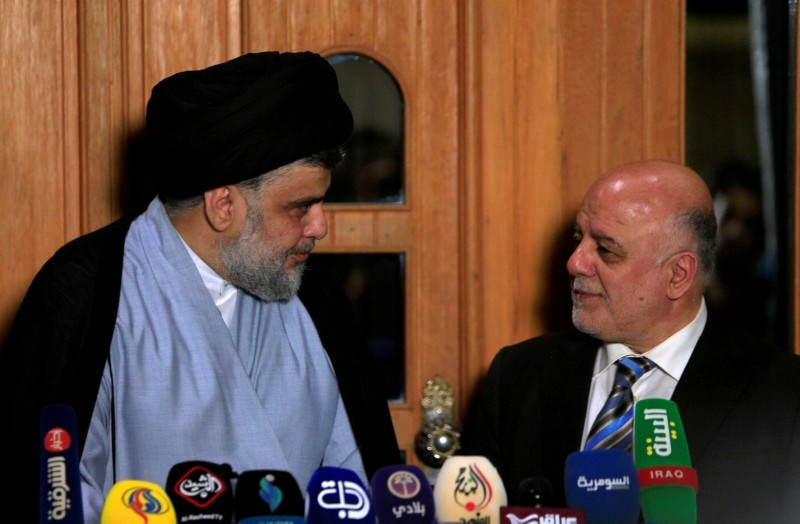 Iraqi Shi'ite cleric Moqtada al-Sadr, who's bloc came first, looks at Iraqi Prime Minister Haider al-Abadi, who's political bloc came third in a May parliamentary election, during a news conference in Najaf, Iraq June 23, 2018. (Reuters Photo)