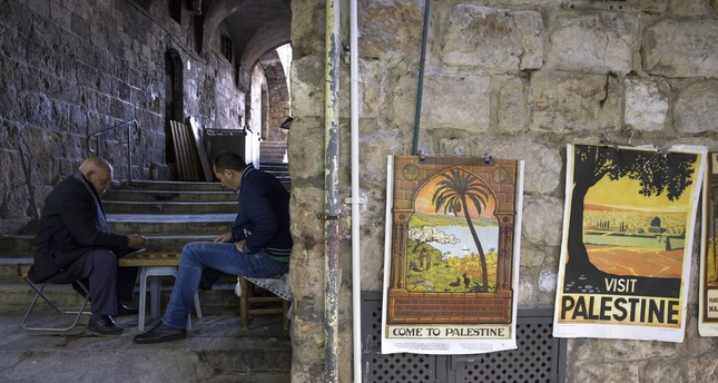 Palestinians in the Moslem Quarter of Jerusalem's Old City pass the time playing dominoes nearby some reproductions of old tourism posters enticing visitors to 'Palestine', on 14 February 2018.  (EPA Photo)