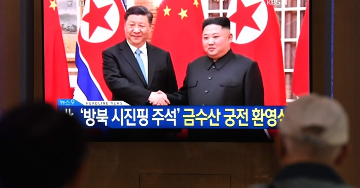 People watch a television news screen showing North Korean leader Kim Jong Un shaking hands with Chinese President Xi Jinping, at Seoul railway station in Seoul on June 20, 2019. (AP Photo)