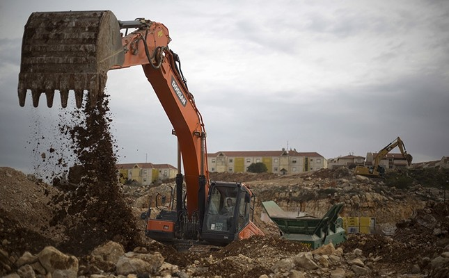Heavy machinery work in a construction site in the West Bank Jewish settlement of Ariel, Wednesday, Jan. 25, 2017.