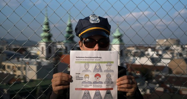 This illustration photo shows a model holding up an information pamphlet about new Austrian restrictions banning wearing of burqas and other items covering face in public places and buildings, in Vienna, Austria on September 29, 2017 (AFP Photo)