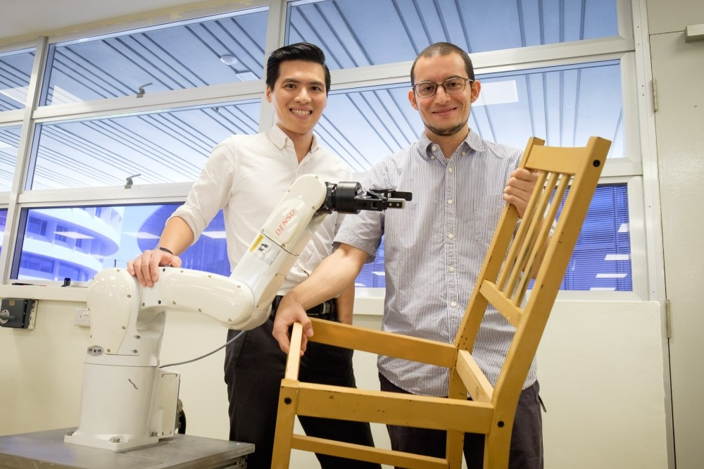 NTU assistant professor Pham Quang Cuong (L) and research fellow Francisco Suarez-Ruiz pose with an autonomous robotic arm capable of assembling IKEA furniture, Singapore.
