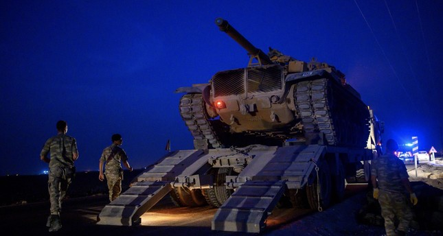 A Turkish army's tank drives down from a truck as the Turkish Armed Forces drive towards the border with Syria near Akçakale in Şanlıurfa province, Oct. 8, 2019.