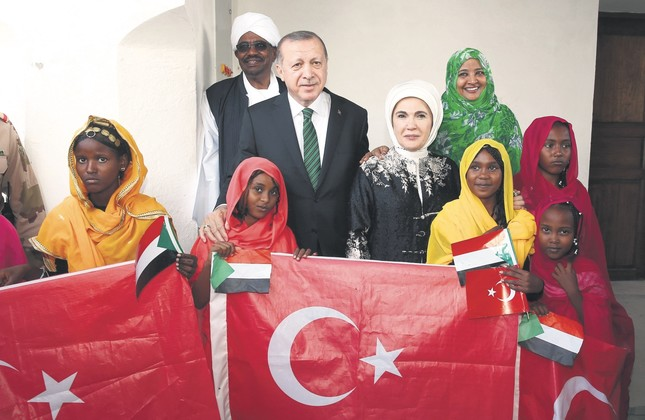 President Erdoğan (C), accompanied by first lady Emine Erdoğan, pose for a photograph with Sudan's President Omar al-Bashir and first lady Widad Babiker Ömer Modawi alongside local people holding the Sudanese and Turkish flags in Port Sudan, Dec. 25.
