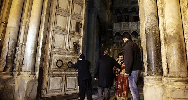 Christian clerics open the doors of the Church of the Holy Sepulchre, traditionally believed by many Christians to be the site of the crucifixion and burial of Jesus Christ, in Jerusalem, Wednesday, Feb. 28, 2018 (AP Photo)