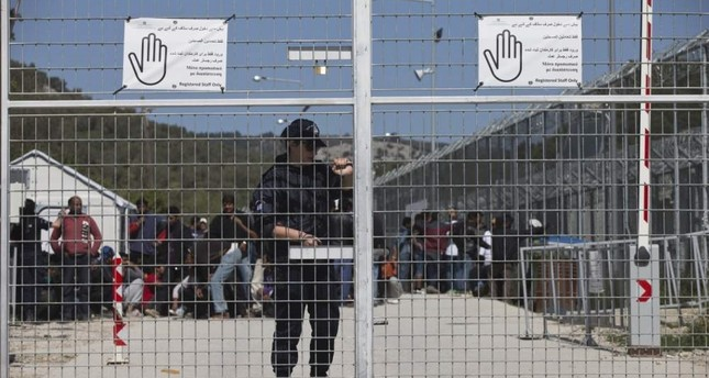 A Greek police officer closes the main gate of Moria camp as behind her refugees and migrants protest inside the entrance of Moria camp in the Greek island of Lesbos, Apr. 5, 2016. AP Photo