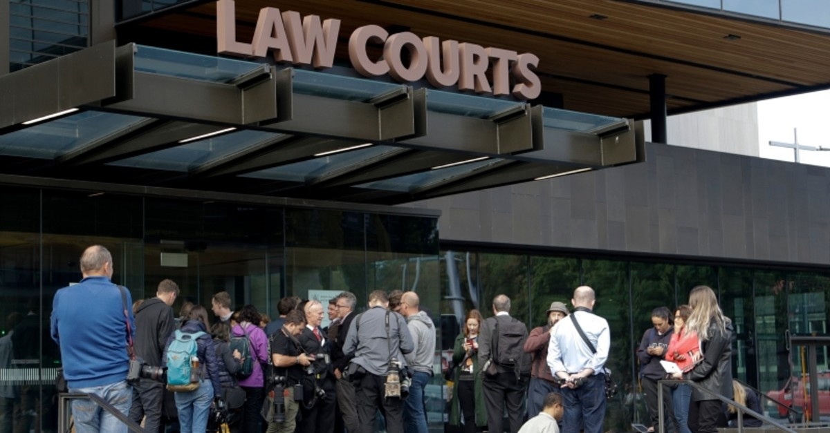 Members of the media wait outside the district court building for word on the man arrested in connection with the mass shootings at two mosques in Christchurch, New Zealand, Saturday, March 16, 2019. (AP Photo)