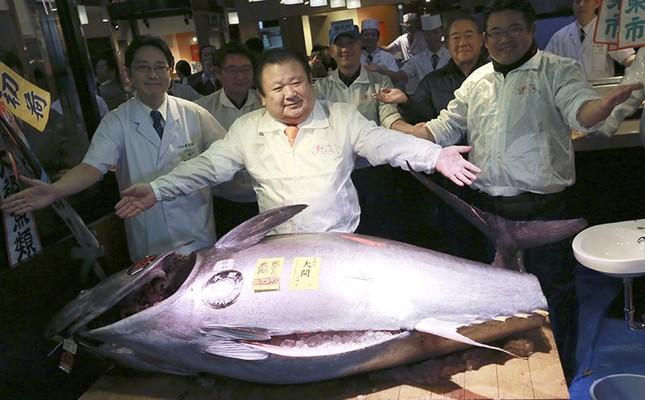 Kiyoshi Kimura, center, president of Kiyomura Co., poses with the bluefin tuna he made a winning bid at the annual New Year auction, at his Sushi Zanmai restaurant near Tsukiji fish market in Tokyo, early Thursday, Jan. 5, 2017. (AP Photo)