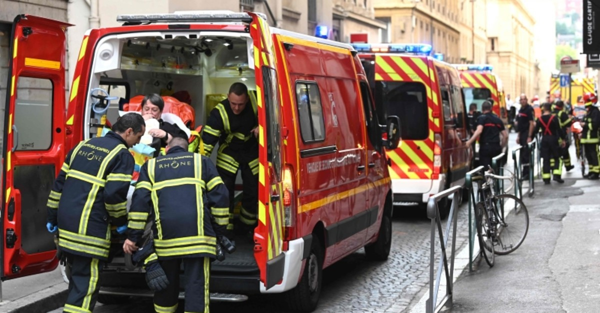 Emergency workers attended to an injured person in the back of an ambulance after a suspected package bomb blast along a pedestrian street in the heart of Lyon, southeast France, the local prosecutors' office said on May 24, 2019 (AFP Photo)