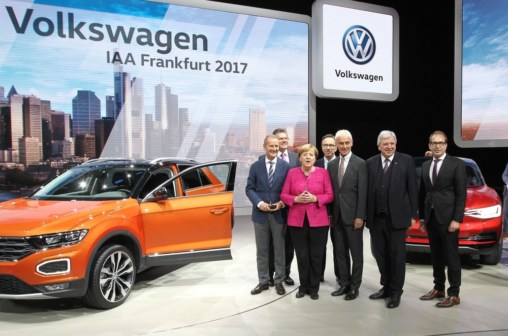 Angela Merkel and Volkswagen CEO Matthias Mueller (3rdR), and the other officials stand next to a VW T-Roc car as they visit the booth of Volkswagen during her inauguration tour of Internationale Automobil auto show, yesterday in Frankfurt am Main.
