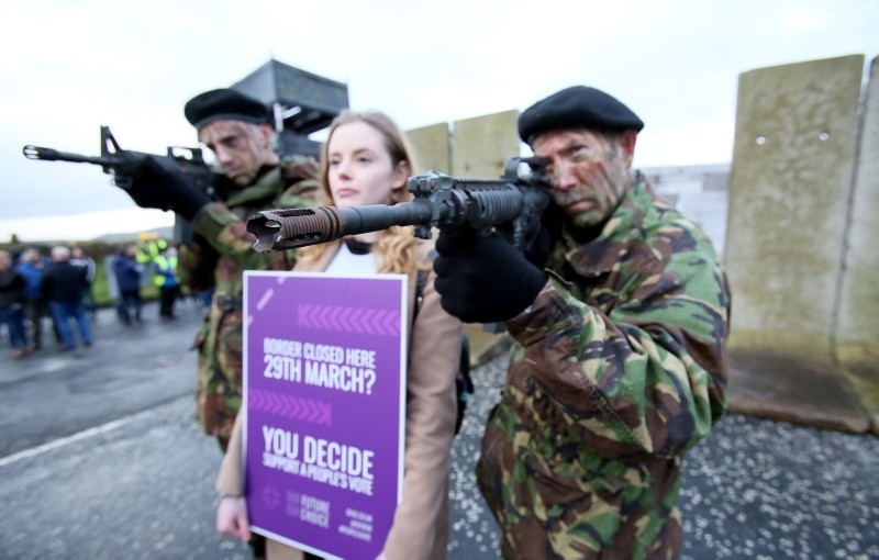 Members of the anti-Brexit campaign group ,Border communities against Brexit,, dressed as British Army Soldiers, pose with a wall installed on a road crossing the border between Northern Ireland and Ireland. (AFP Photo)