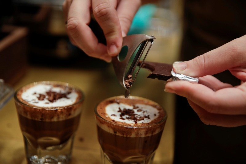 In this photo taken on Tuesday, Sept. 4, 2108, a waiter adds chocolate to coffee cups, at the Starbucks store in Milan, Italy. (AP Photo)