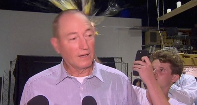 In this image made from video, a teenager breaks an egg on the head of Senator Fraser Anning while he holds a press conference, Saturday, March 16, 2019 (AP Photo)