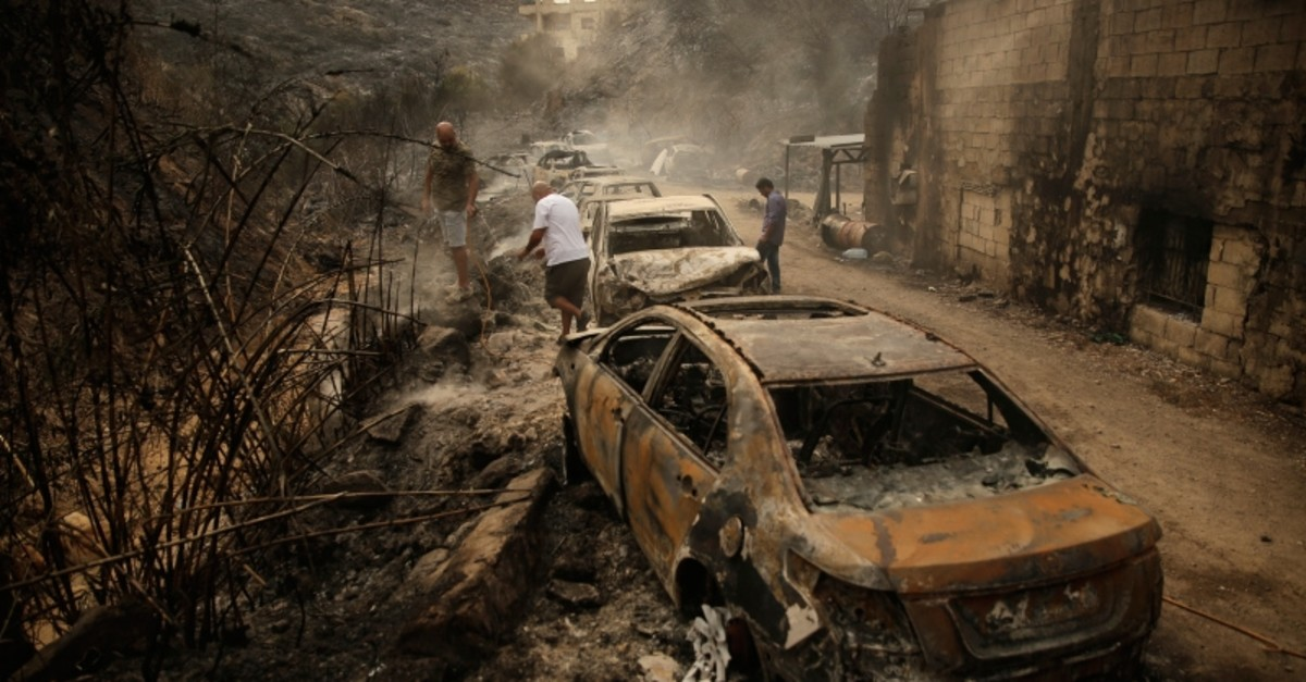 People inspect the remains of cars and shops that were burned in a wildfire overnight, in the town of Damour just over 15km (9 miles) south of Beirut, Lebanon, Tuesday, Oct. 15, 2019. (AP Photo)