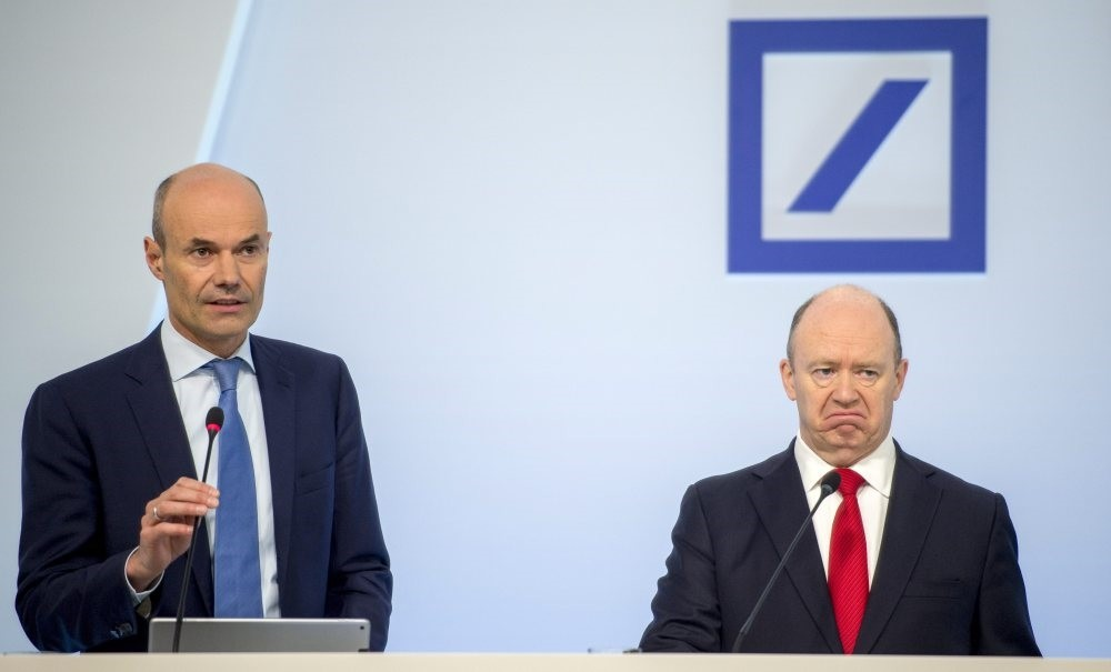 Deutsche Bank CFO Marcus Schenck (L) speaks next to CEO John Cryan (R) during the annual press conference in Frankfurt yesterday. The bank reported a net loss of 1.9 billion euros for the fourth quarter of 2016 plus the second consecutive loss for a
