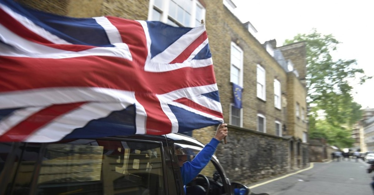 A taxi driver holds a U.K. flag as he celebrates following the result of the EU referendum, London, June 24, 2016.