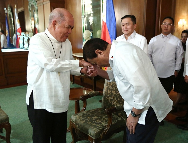 Handout photo from the Presidential Photographers Division shows Philippine President Rodrigo Duterte (R) greeting Archbishop Romulo Valles before a meeting in Malacanang presidential palace in Manila, Philippines, July 9, 2018. (EPA Photo)