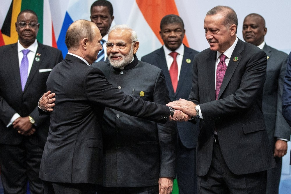 Russian President Putin (L), Indian Prime Minister Modi (C) and President Erdou011fan (R) talk during a group picture at the BRICS summit, Johannesburg, South Africa, July 27.
