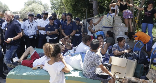 Italian police stand by evicted Roma people and their belongings outside the Camping River village, Rome, July 26.