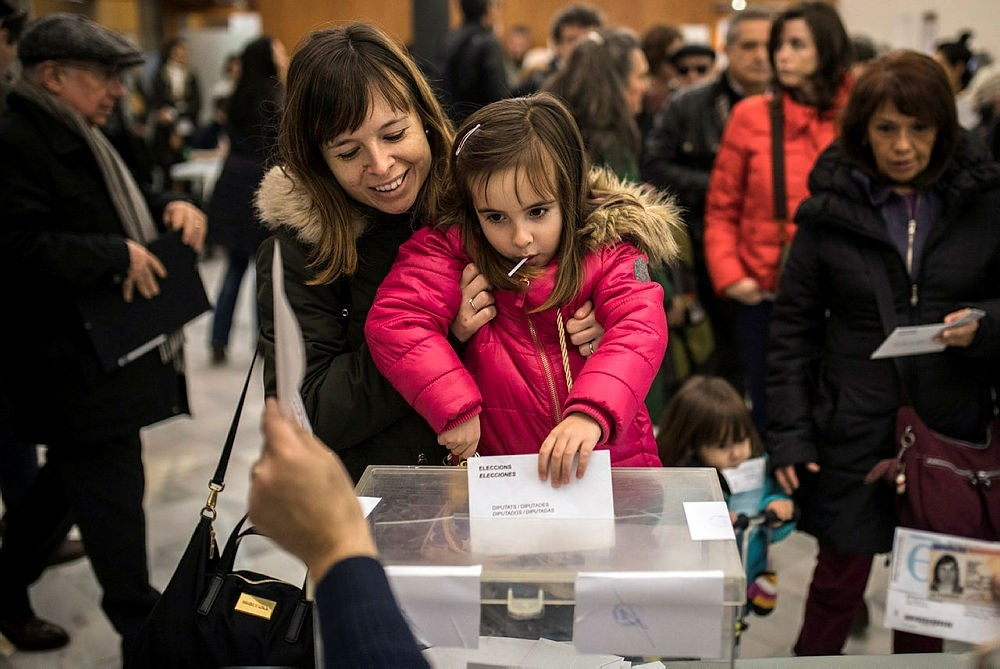 A woman has her child casting the ballot for her for the Catalan regional elections at a polling station in Barcelona, Spain, Thursday, Dec. 21, 2017. (AP Photo)