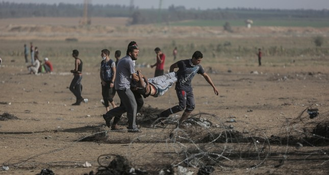 Palestinians protesters carry a wounded protester in clashes during a Friday protest near the border in the east of Khan Younis town southern Gaza Strip on, 08 June 2018. (EPA Photo)