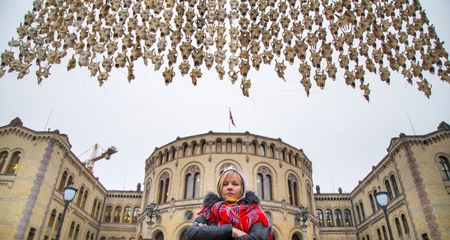 Sami artist Maret Anne Sara stands near her art piece of 400 reindeer skulls hanging in front of the Parliament building in Oslo, Norway ( AP Photo)