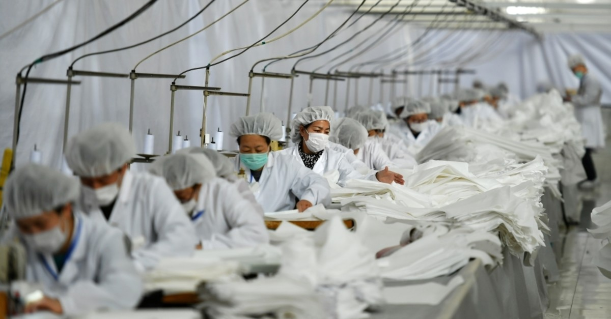 Employees work on a production line manufacturing protective suits at a clothing factory, as the country is hit by an outbreak of the novel coronavirus, in Shijiazhuang, Hebei province, China Feb. 17, 2020. (Reuters Photo)