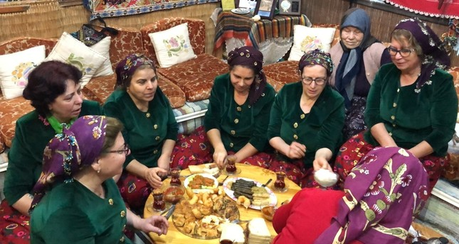 Women in traditional cloths enjoy the meals they have prepared using their grandmothers' recipes.