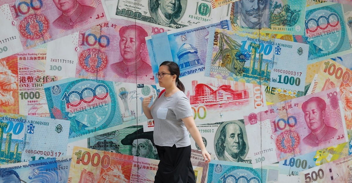 A woman walks by a money exchange shop decorated with different currency banknotes at Central, a business district in Hong Kong, Aug. 6, 2019.