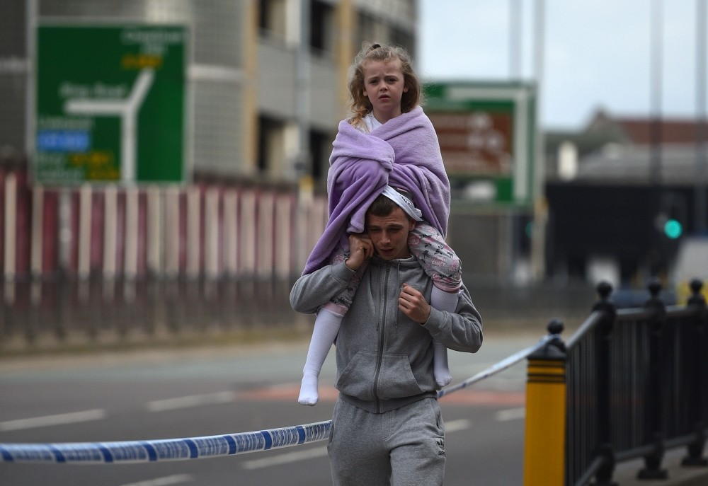 A man carrying a young girl on his shoulders near the Victoria station in Manchester following the deadly terror attack at the Ariana Grande concert on May 23.