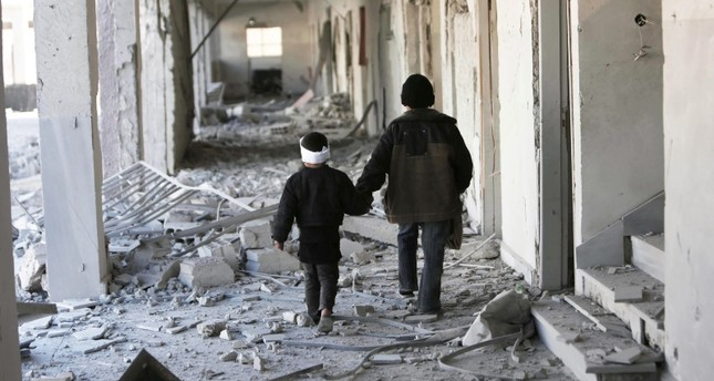 Two children walk through the corridors of a destroyed school in Eastern Ghouta, Syria. (Save the Children via AP)