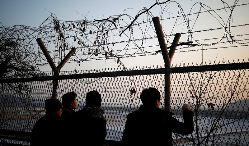 People look toward the north through a barbed-wire fence near the demilitarized zone separating the two Koreas, in Paju, South Korea. (Reuters Photo)