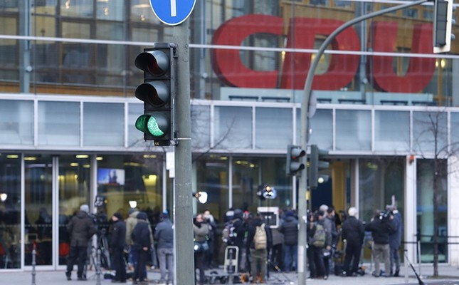 A traffic light shows green when journalists wait outside the CDU headquarters during the coalition talks on forming a new German government between Angela Merkel's CDU and the Social Democratic Party in Berlin, Germany, Feb. 7, 2018. (AP Photo)