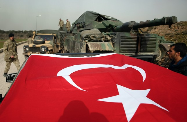 Turkish  soldiers prepare tanks and armored personnel carriers at a staging on the Turkish-Syria border, Jan. 22.