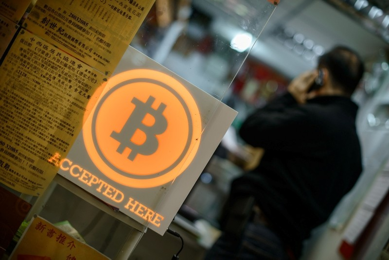 This file picture taken on February 28, 2014 shows a man talking on a mobile phone in a shop displaying a bitcoin sign during the opening ceremony of the first bitcoin retail shop in Hong Kong. (AFP Photo)