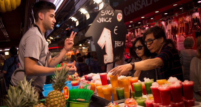 Two tourists buy some juice at 'La Boqueria' market in Barcelona. Spain's government said it could lower its forecast for next year's economic growth if the crisis over Catalonia's independence drive persists.