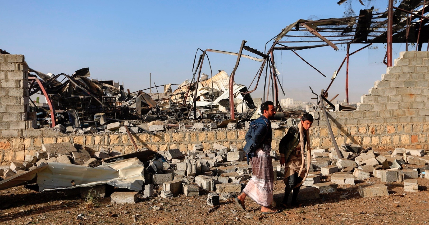Civilians inspect the damage at a factory after a reported airstrike by the Saudi-led coalition, Sanaa, Jan. 20, 2019.