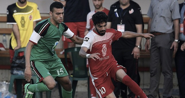 Palestinian Ahli al-Khalil player Fadi Zeidan (R) and Itihad Al-Shejaeiya player Mustafa Hasaballah (L) fight for the ball during a football match between the Ahli al-Khalil and Itihad Al-Shejaeiya in Al Yarmouk stadium in Gaza City (EPA Photo)