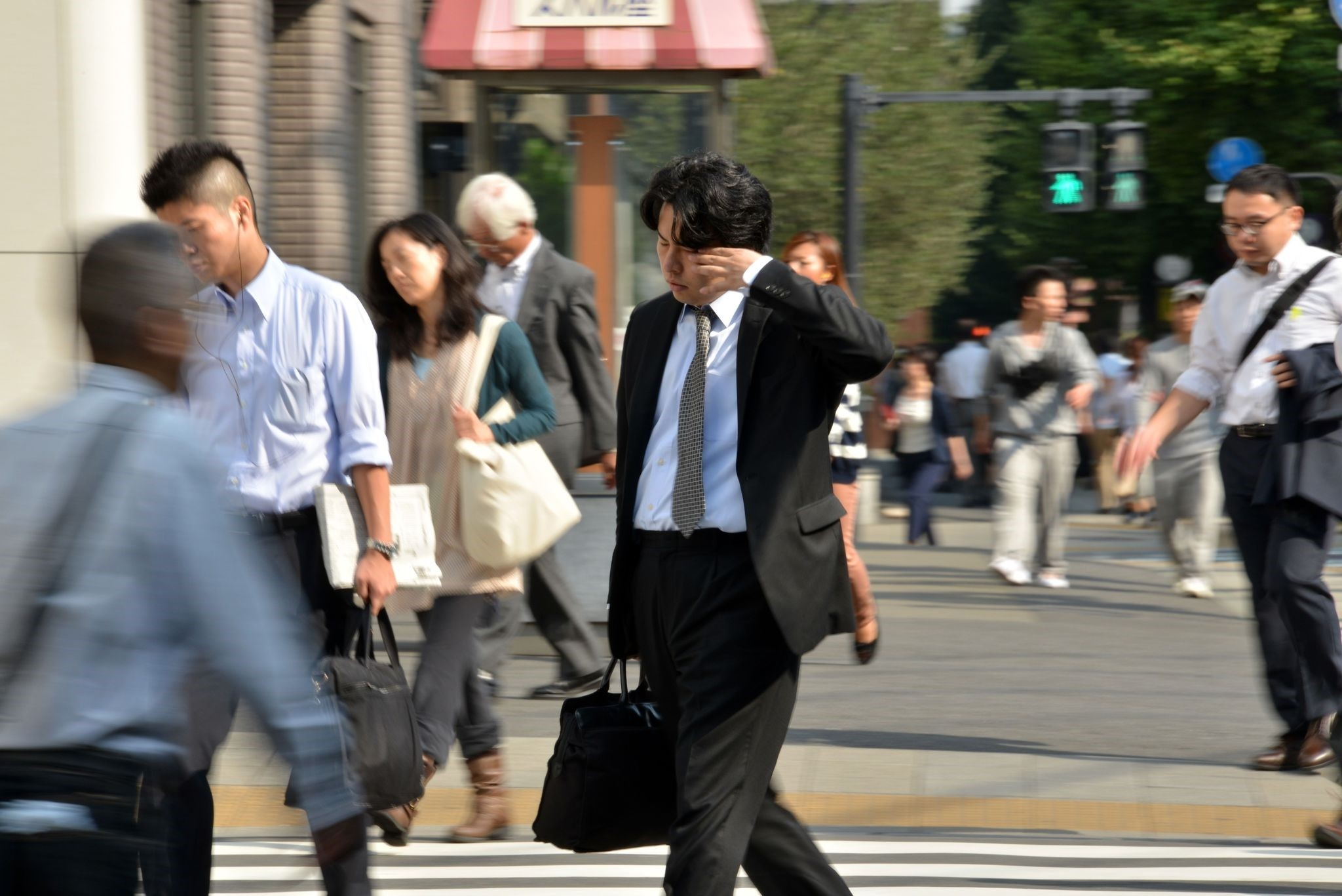 A Japanese businessman, called a salaryman, rubbing his eyes as he heads to his office in Tokyo.