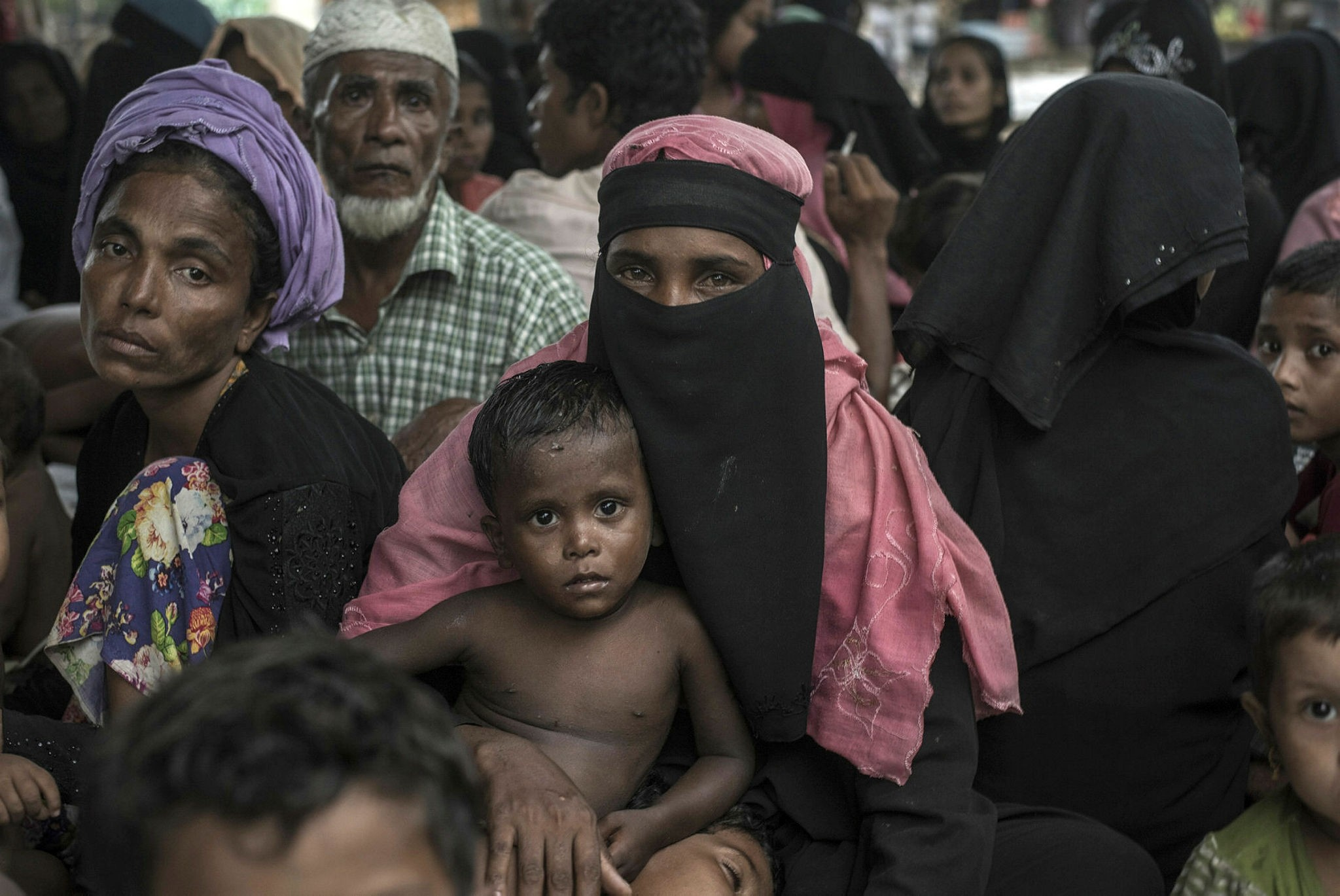 Rohingya Muslim refugees take shelter from the rain at the registration center in Teknaf in Bangladesh's Ukhia district, Oct. 6.