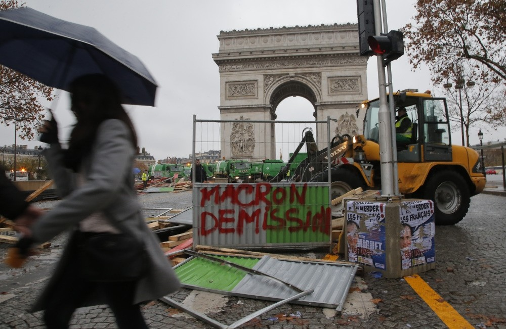 A bulldozer demolishes a makeshift barricade in the aftermath of a protest against rising fuel taxes on the Champs-Elysees avenue, Paris, Nov. 25.