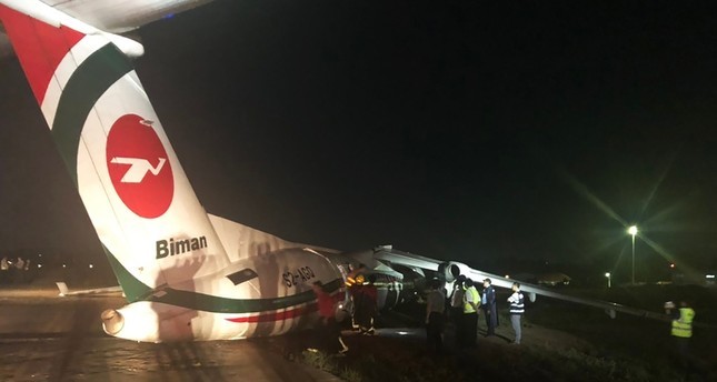 This handout picture taken and released by Myanmar Department of Civil Aviation on May 8, 2019 shows a Biman Bangladesh airlines passenger after it slid off a runway at Yangon International airport in Yangon. (AFP Photo)