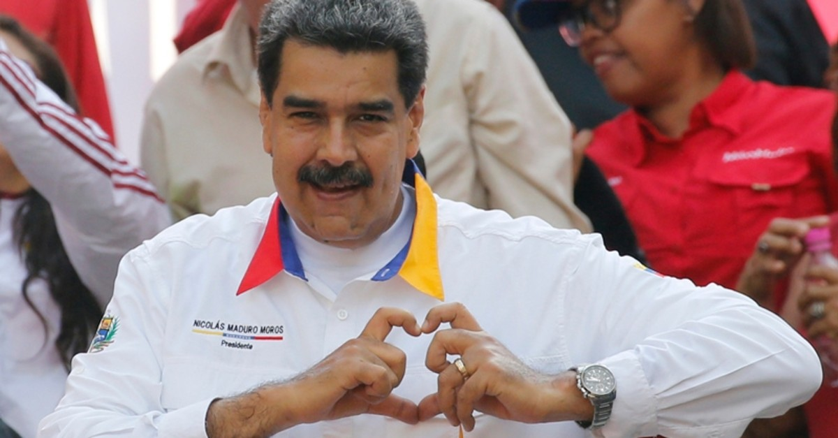 Venezuela's President Nicolas Maduro gestures a heart symbol to supporters outside Miraflores presidential palace in Caracas, Venezuela, Monday, May 20, 2019. (AP Photo)
