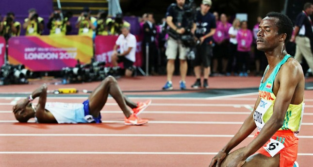 Second placed Mo Farah (L rear) of Great Britain lies on the track after he was beaten by winner Muktar Edris (R) of Ethiopia in the men's 5,000m. (EPA Photo)