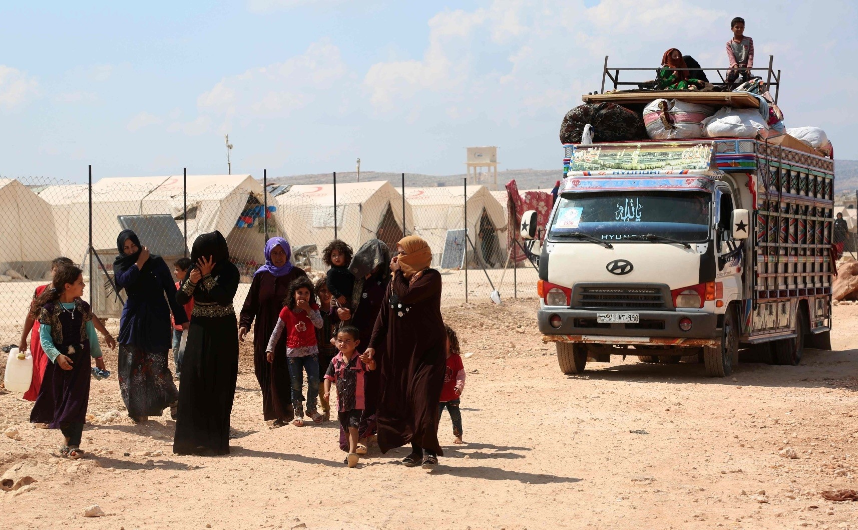 Displaced Syrians arrive with their belongings to a camp in Kafr Lusin, near the border with Turkey in the northern part of Syriau2019s Idlib province, Sept. 9.