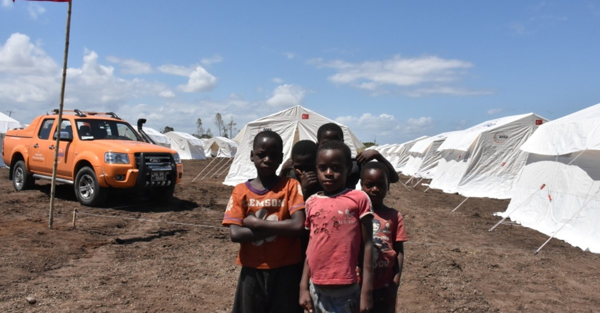 Children pose in front of tents set up by AFAD.